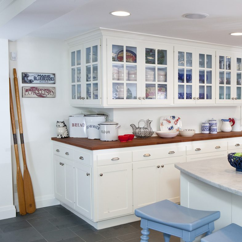 "A view of the large, bright kitchen with large ""L"" island and lots of cabinets and cupboards."