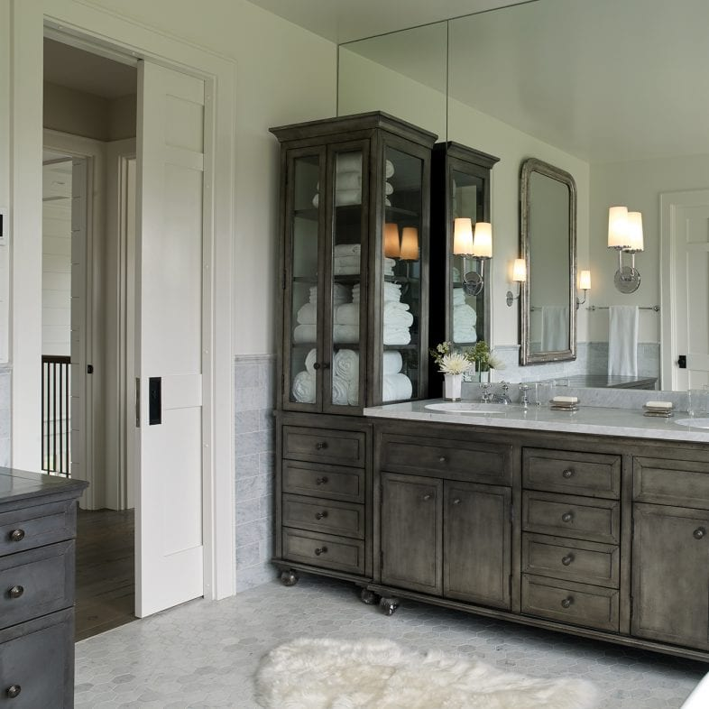 Large master bathroom with mirror wall, large hutches, marble tile flooring, and storage space.