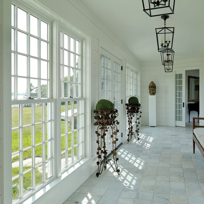 A view of the hallway with access to the backyard, featuring marble flooring and farmhouse-style lighting