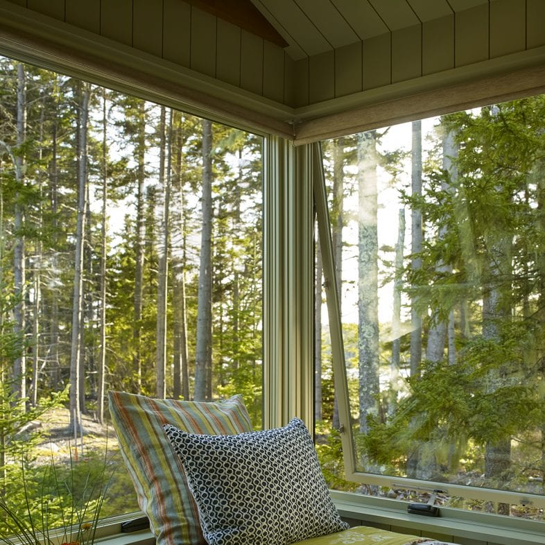 Large windows offering expansive views of the trees at Capitol Island
