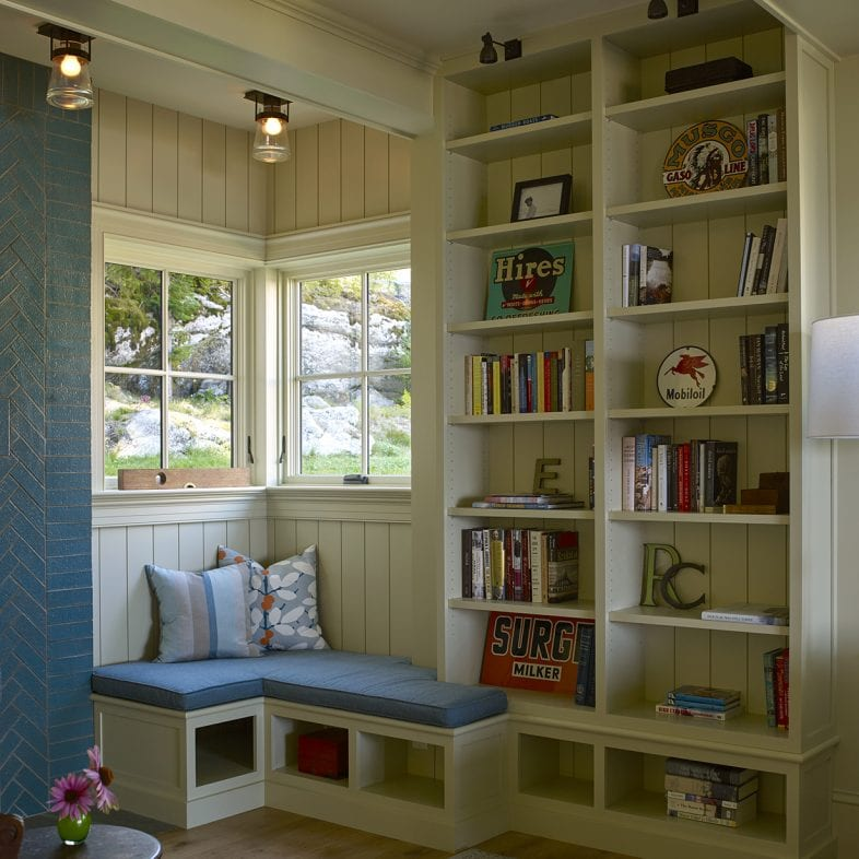 Reading nook with built-in bookshelves and views of nature at Capitol Island