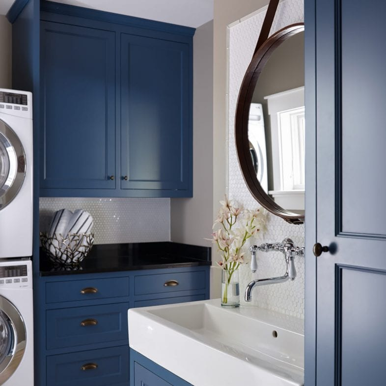 Spacious blue laundry room with sink and stackable washer and dryer at Casino Cottage