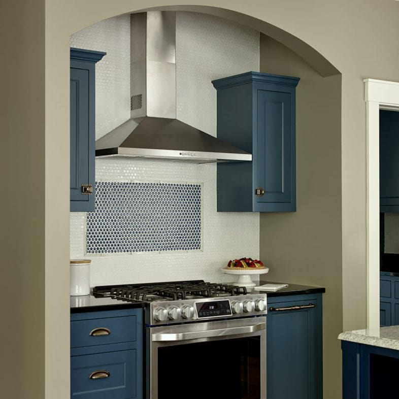 Blue kitchen with arch above the stove at Casino Cottage