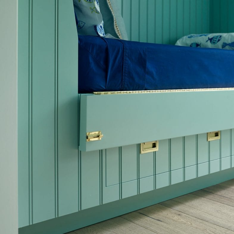 Under-bed storage and drop-down piece for easy access to change bedding at Casino Cottage