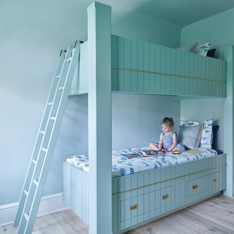 Bunkbeds with ocean life theme and ladder at the foot of the bed.