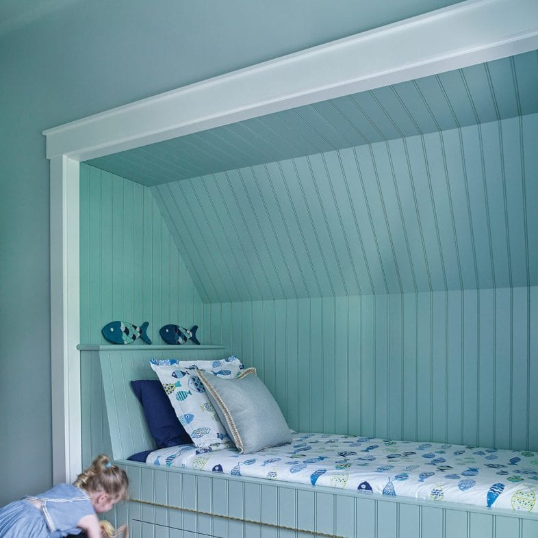 A built-in bed with pull-out drawers and ocean life theme.
