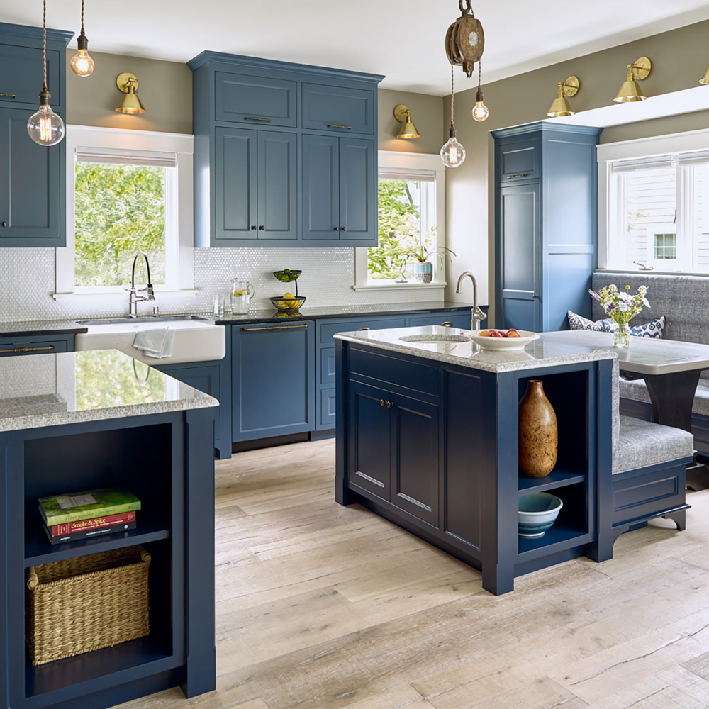 Navy kitchen with unique lighting, light stain flooring, and sitting area.