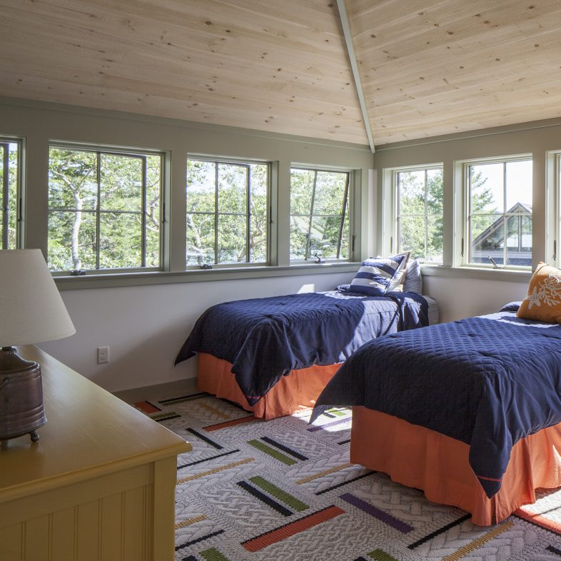 Guest bedroom with expansive windows at the Cross Point Cottages