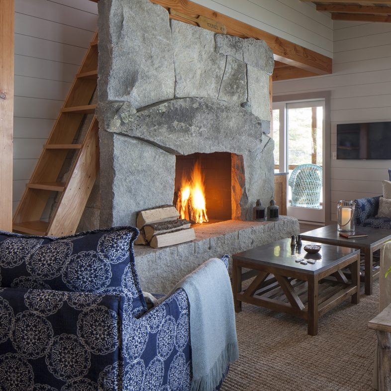 Cozy living space with a large stone fireplace at the Cross Point Cottages