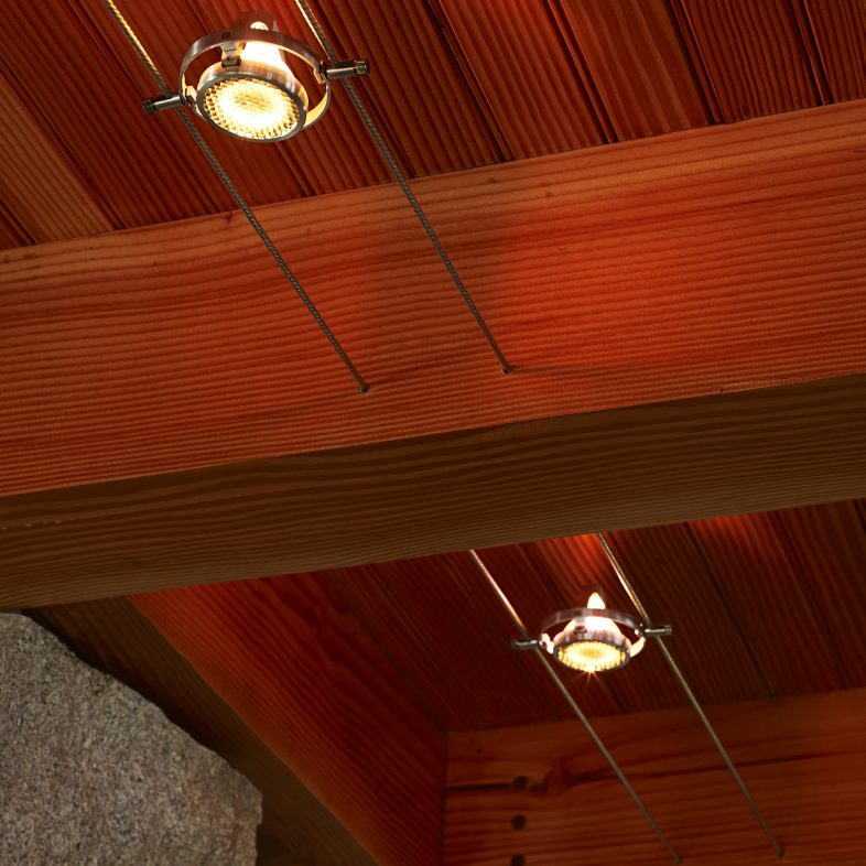 Elegant track lighting through wooden beams at the Cross Point Cottages