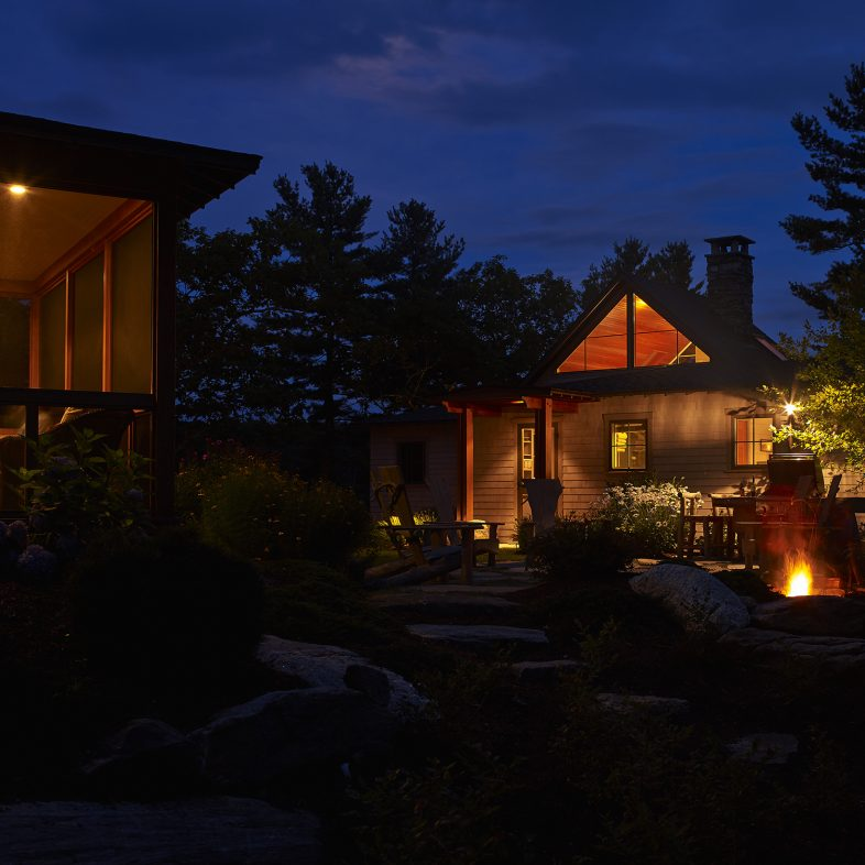 View of the Cross Point Cottages at night with a fire lighting up the patio space