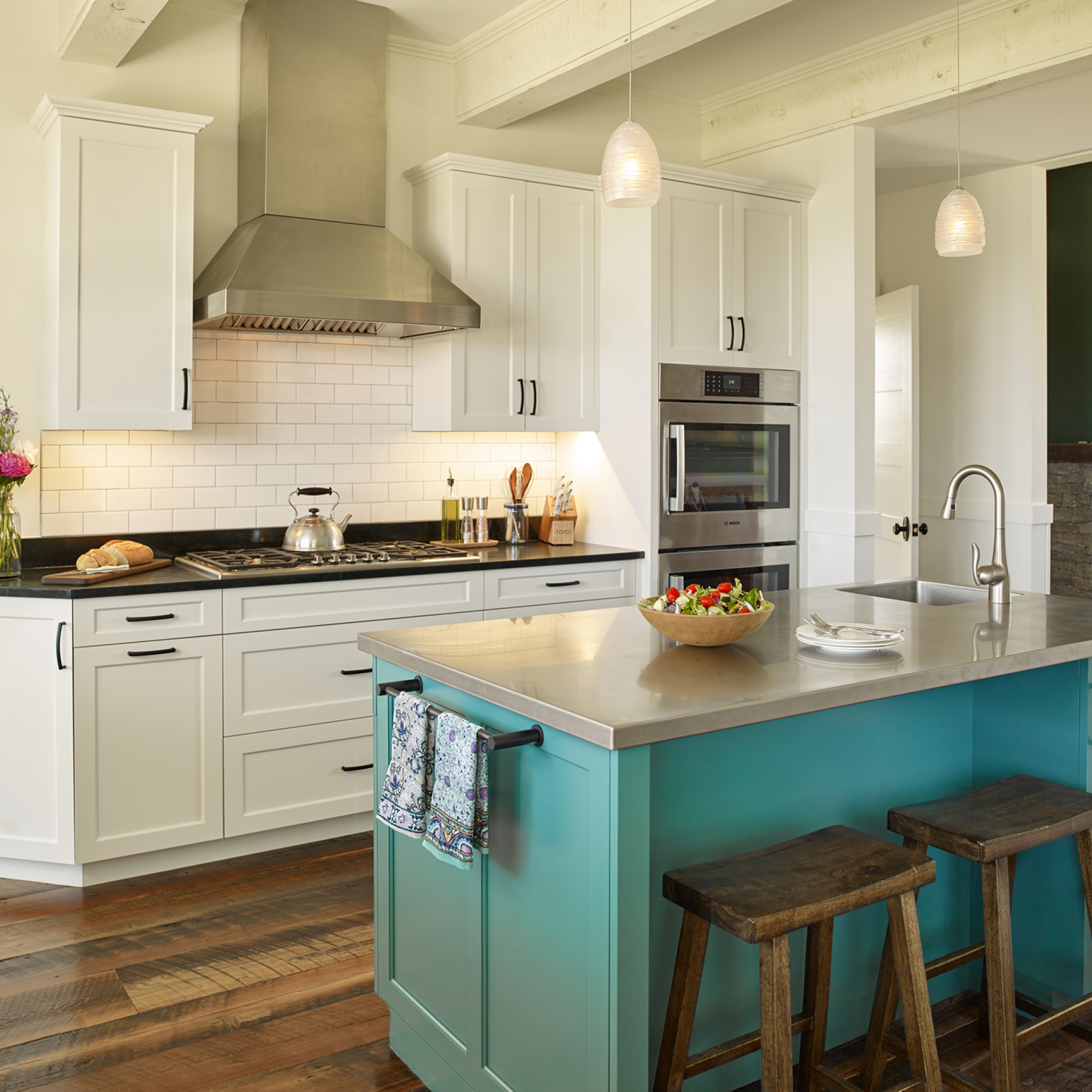 A large inviting kitchen with a beautiful blue island and hardwood floors.