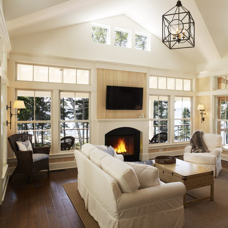Large bright living room with rustic chandelier, large windows for unobstructed coastal views, and large fireplace.