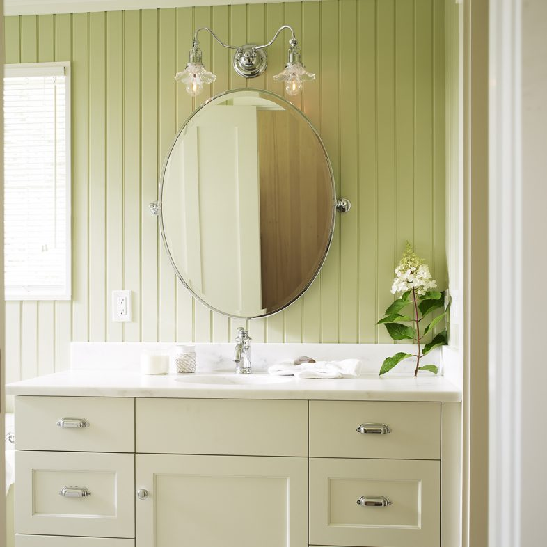 A modern vanity with marble countertop and relaxing sage hue scheme.