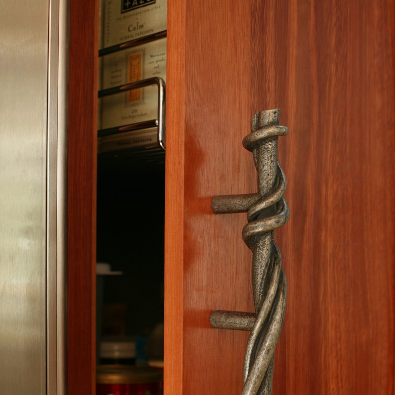 Unique twisted metal handle in the kitchen with walnut stain on doors.