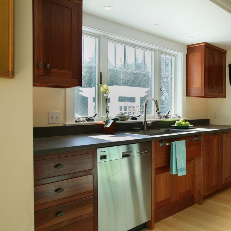 A view of the kitchen with dark countertops, silver appliances, dark wood stain, and blue accent color.