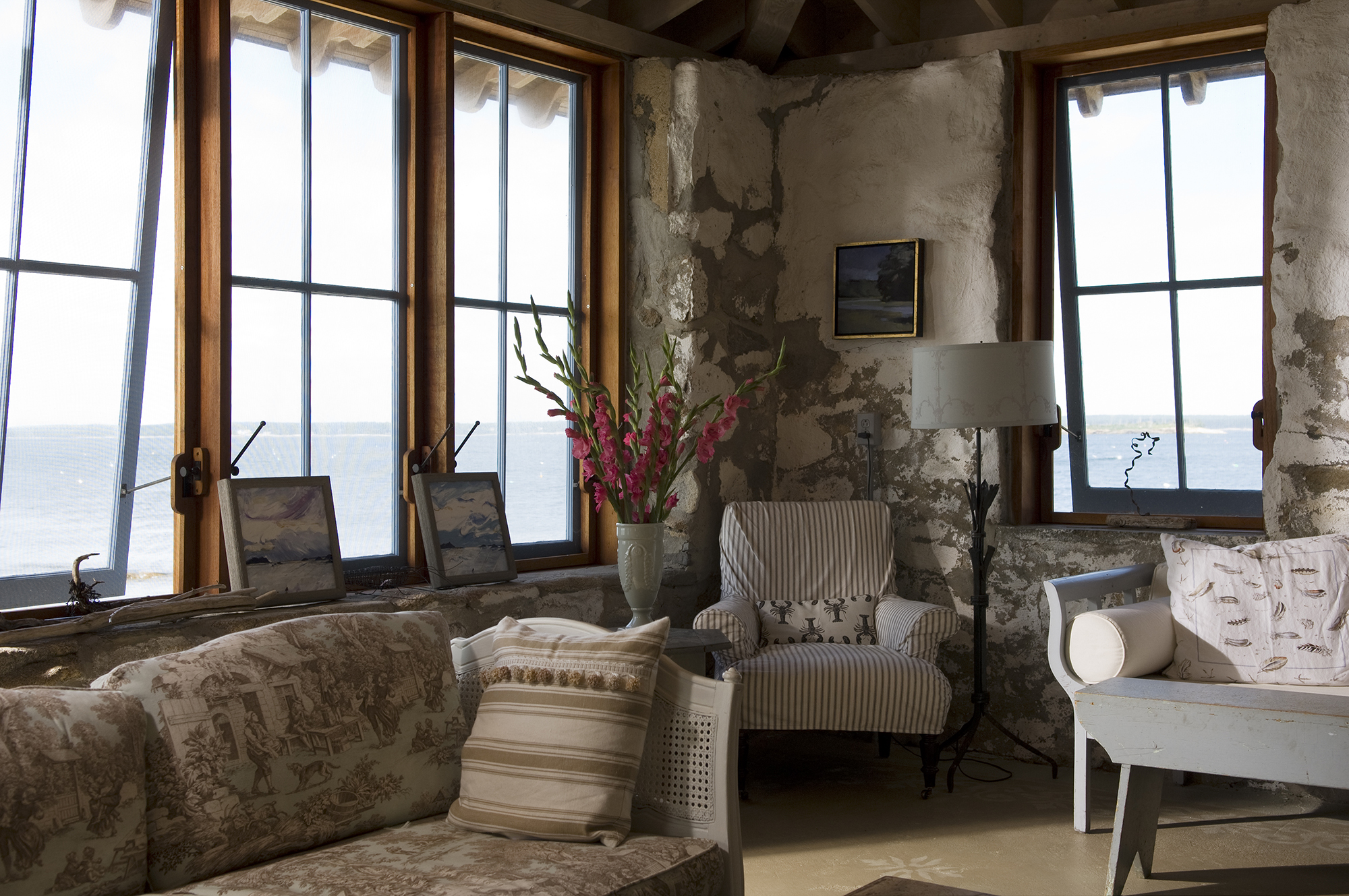 Expansive windows offering panoramic water views in the living area at Hunting Island Cottage