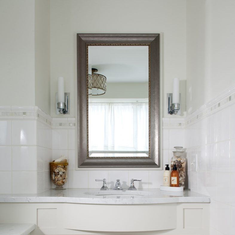 White bathroom with wooden accent mirror at Brambletye