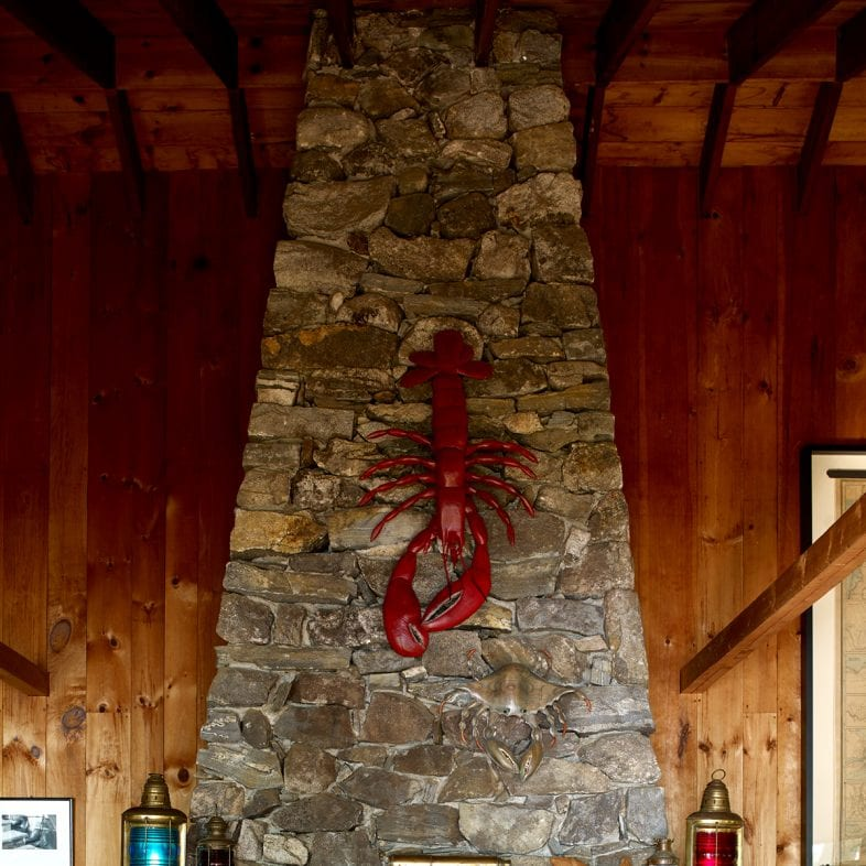 Tall stone fireplace with lobster decor at Little Acorn Cottage