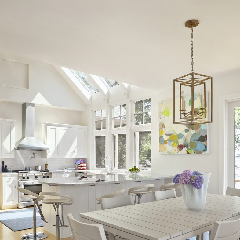 Large kitchen and dining area with natural light and contemporary pendant