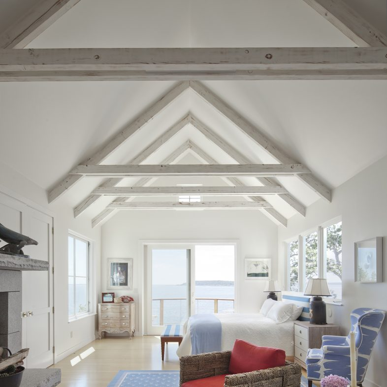Bright bedroom with sitting area, fireplace, and cathedral ceilings.