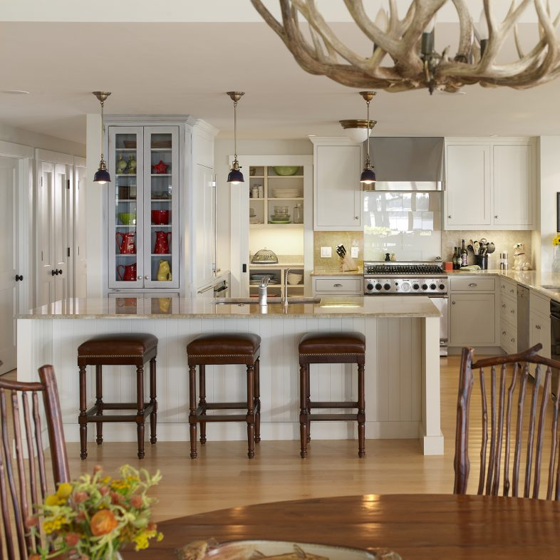 An antler chandelier over the dining table, with open sightlines to the bright kitchen