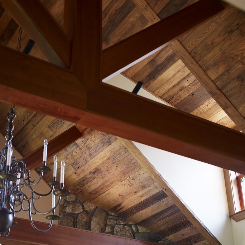 A close-up of the exposed beams, wood accent ceiling, and stone fireplace.