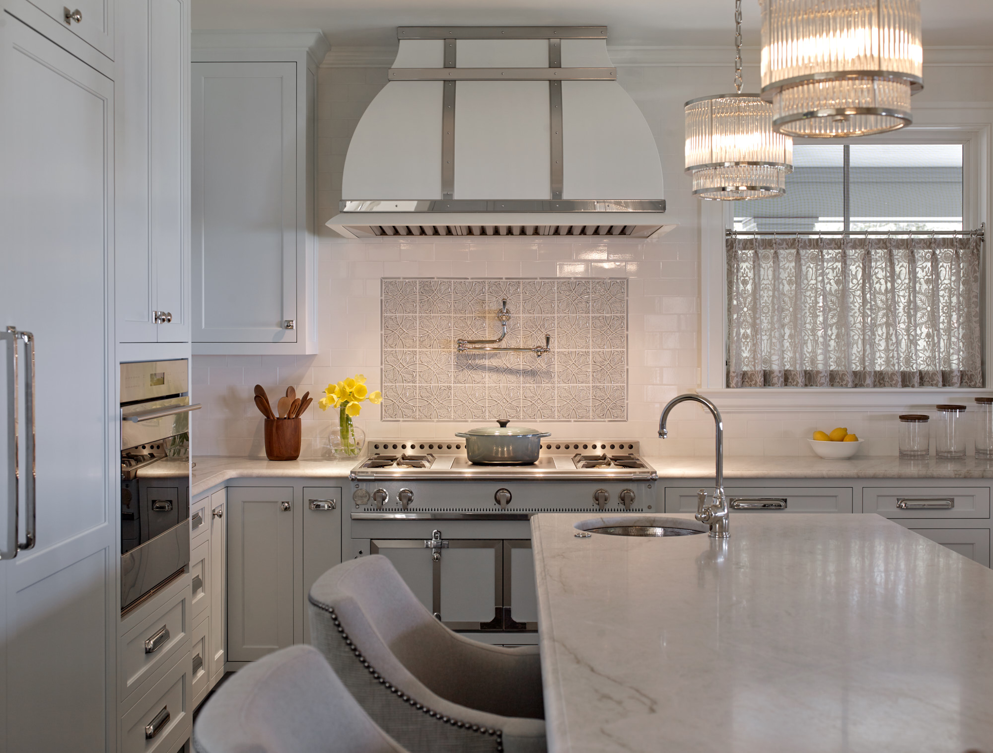 A white and marble kitchen with an island and a 1908 La Cornue stove
