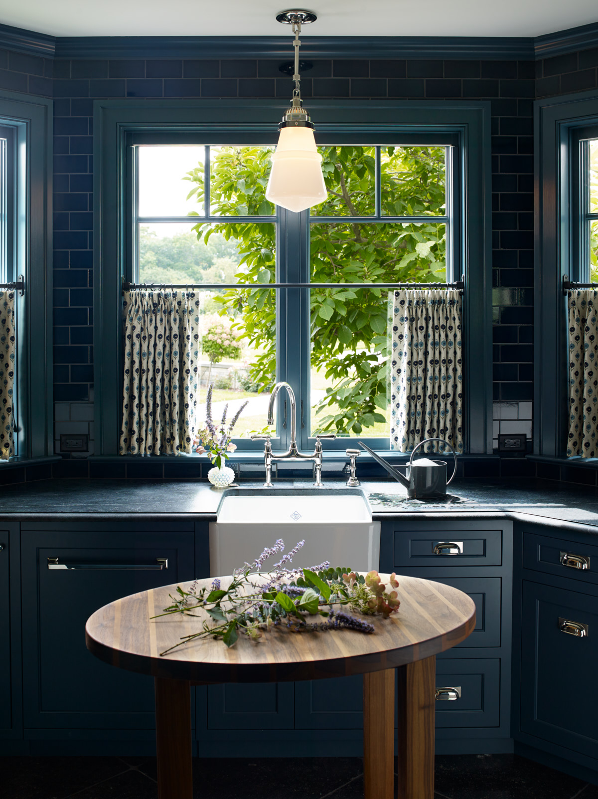 A view of the kitchen area that highlights the unique light fixture and deep blue theme.