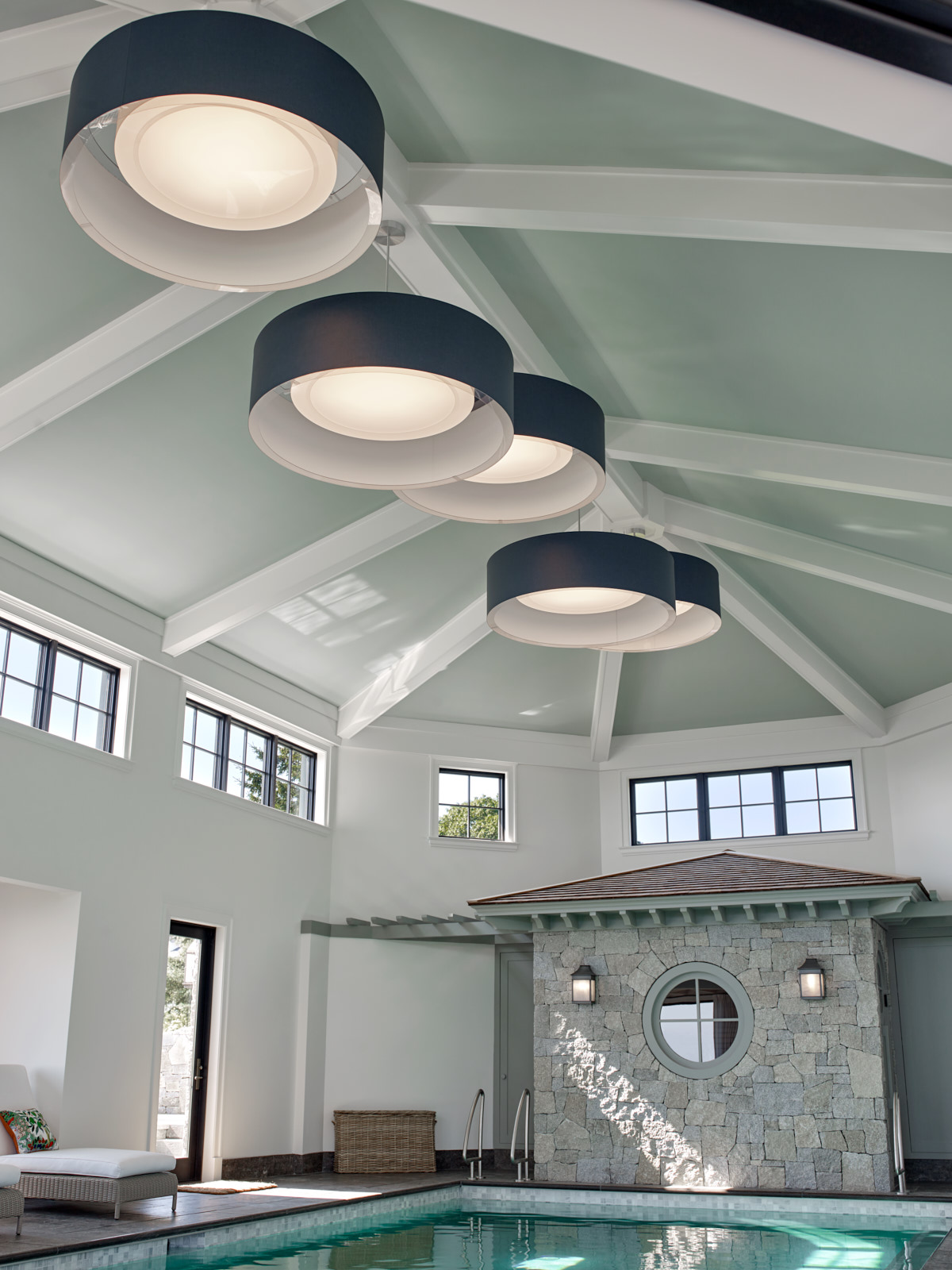 The modern lighting completes the look with the cathedral ceiling of this indoor pool and sauna room.