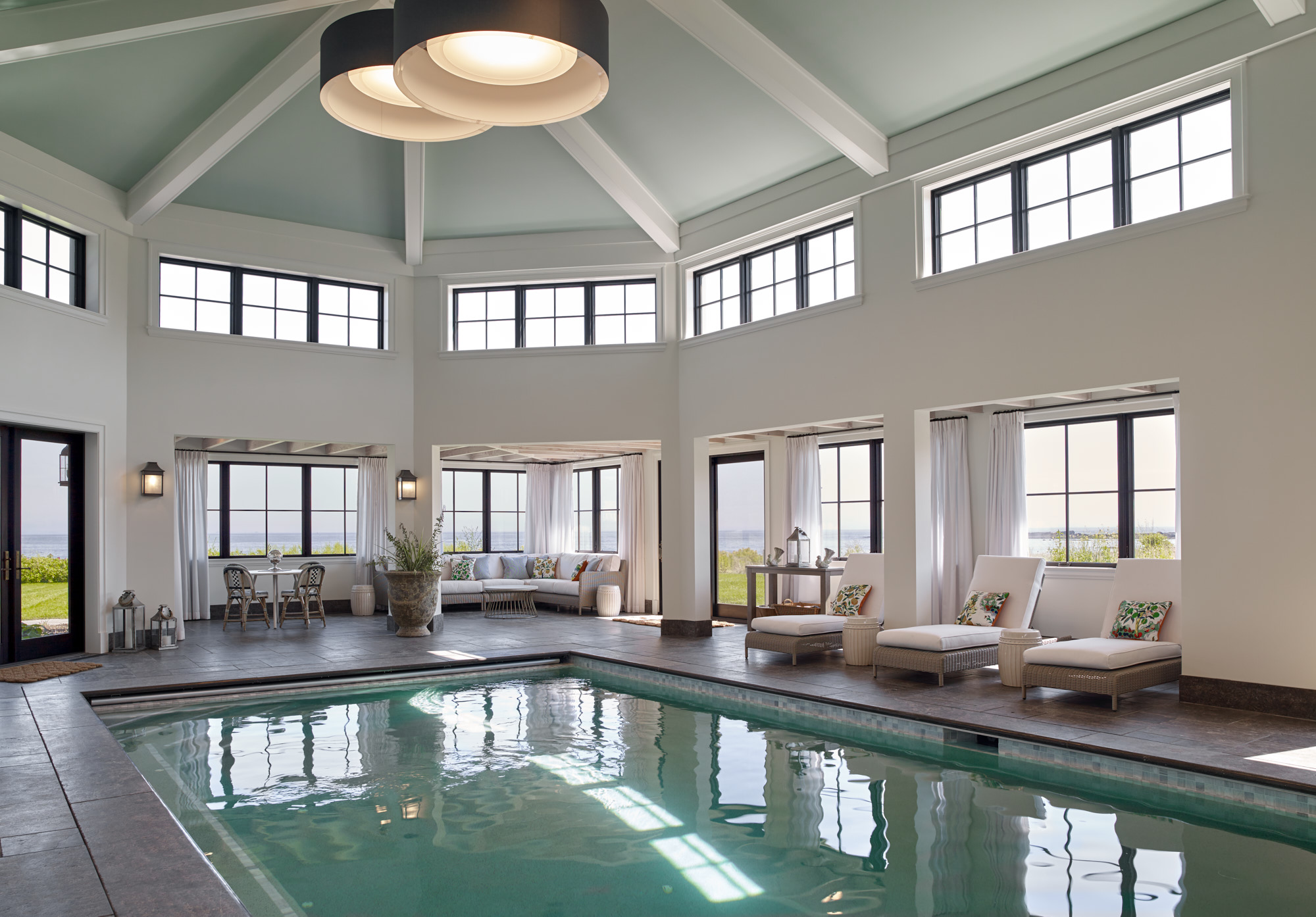 Modern indoor pool room with natural lighting and a cathedral ceiling.