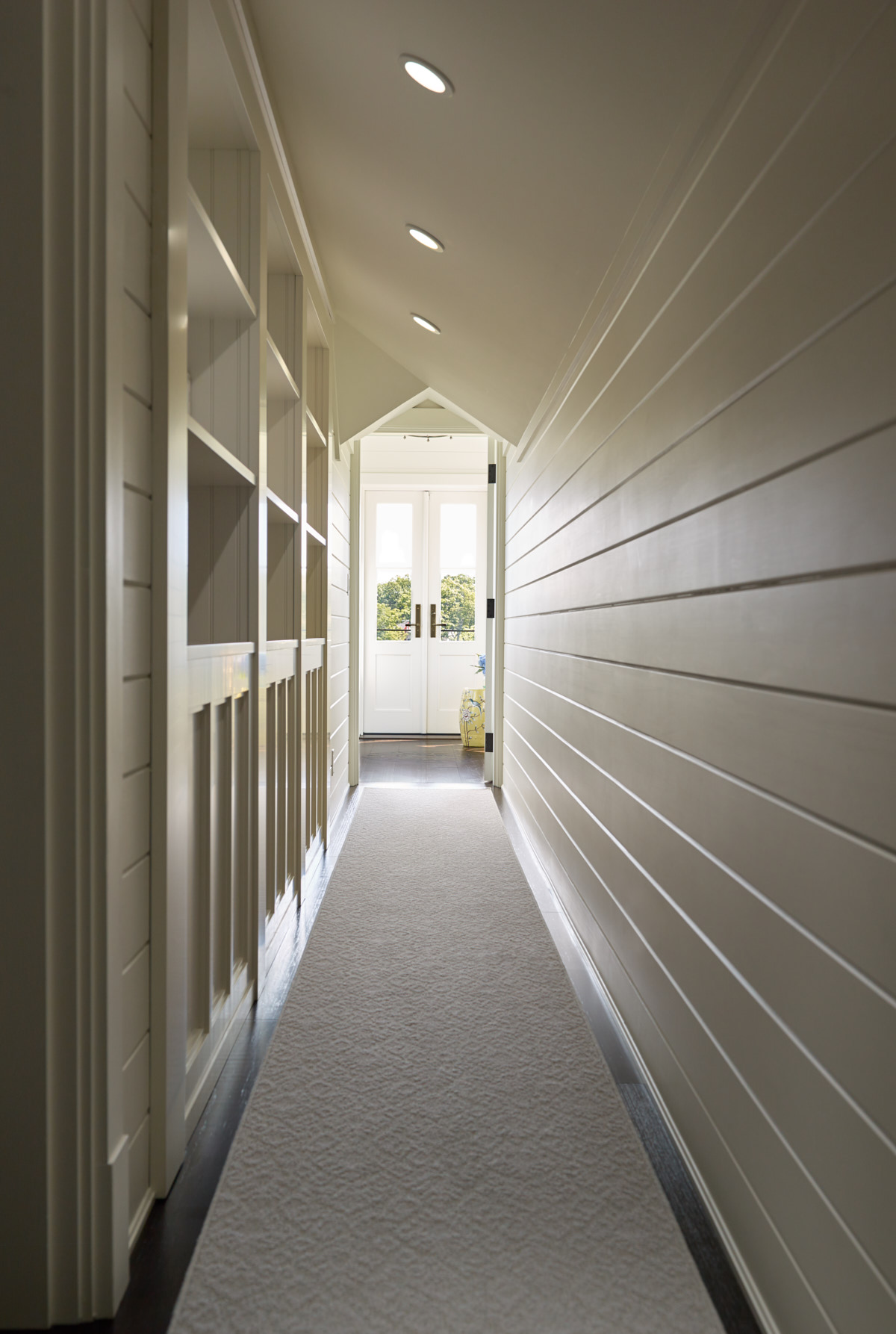 A view of the hallway with storage and direct sight to the french doors.
