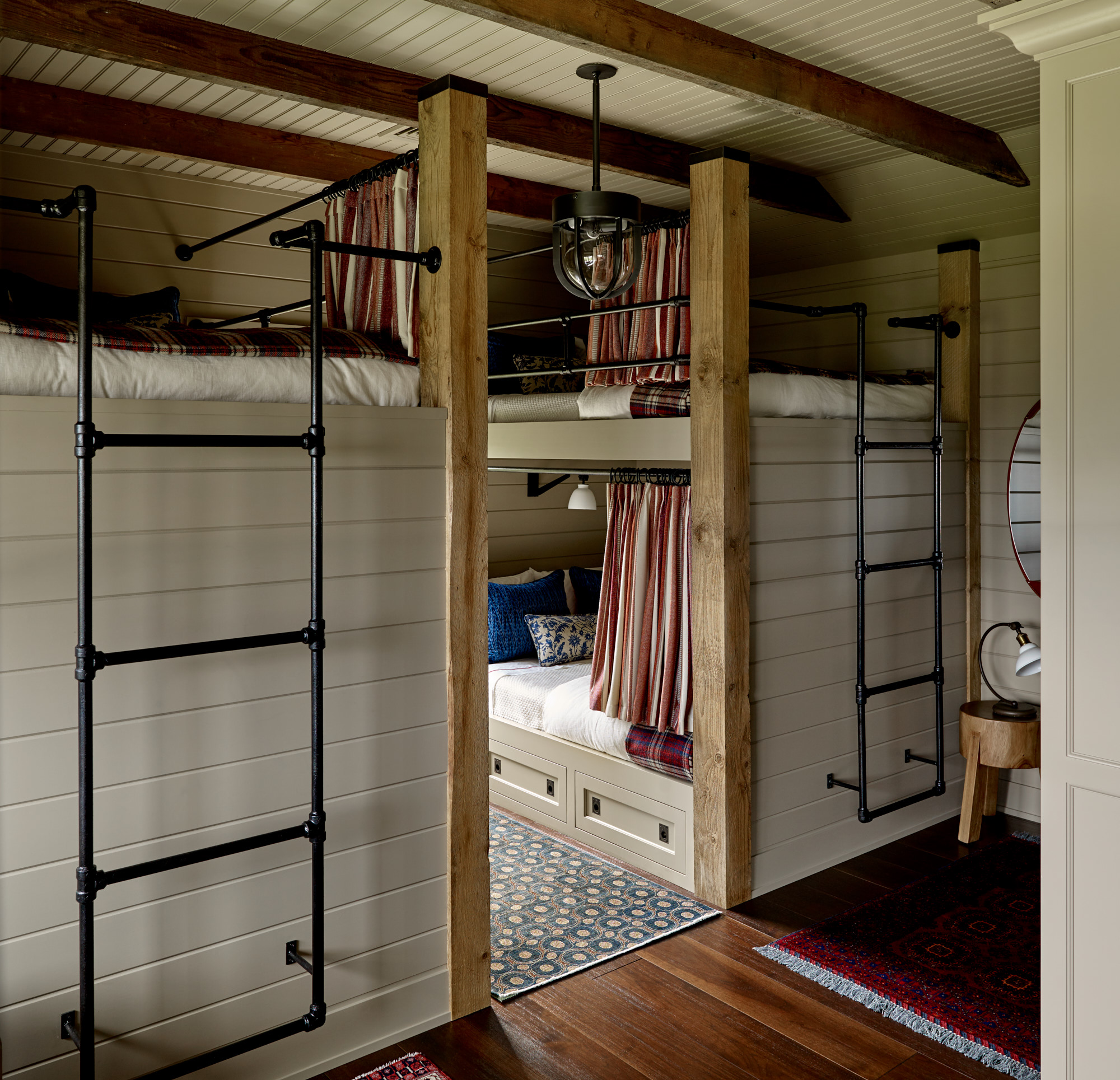 Bunkbeds with iron ladders at the foot of the beds.