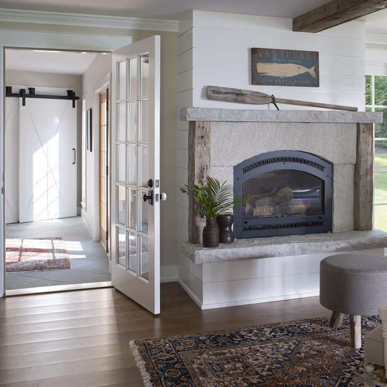 Simple stone fireplace in the living area at the Boothbay Farmhouse