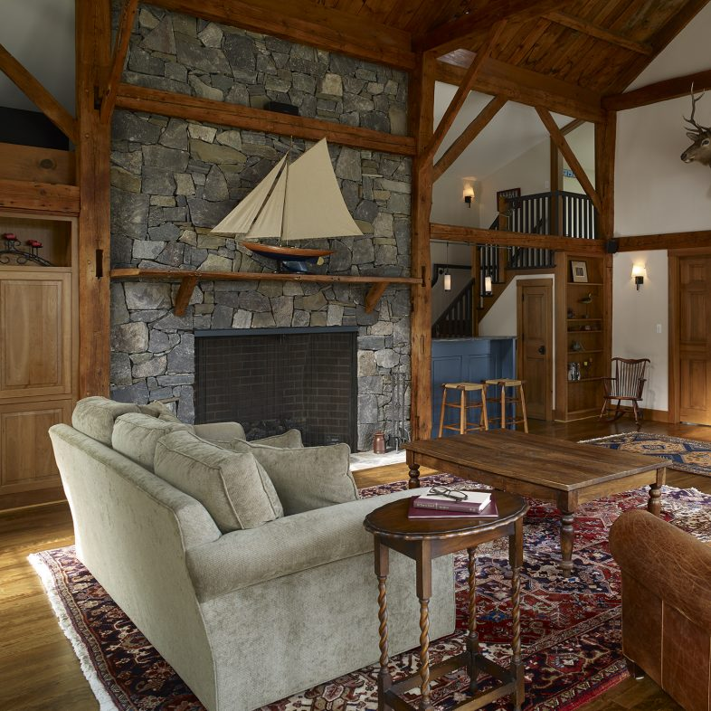 Living space at the Boothbay Farmhouse with a large stone fireplace