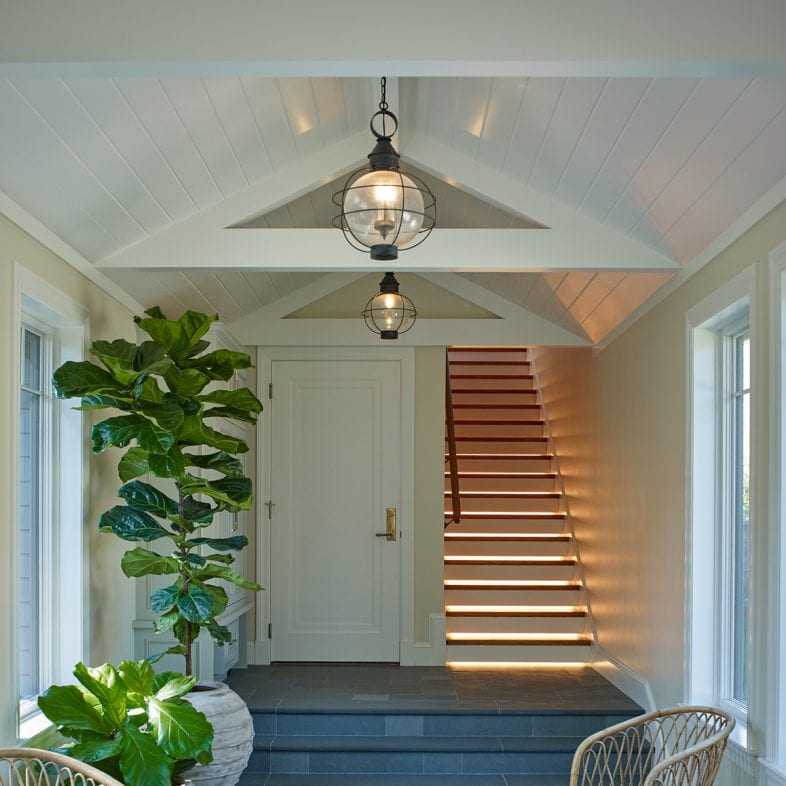 Stairs with light coming through and decorative beams along the ceiling.