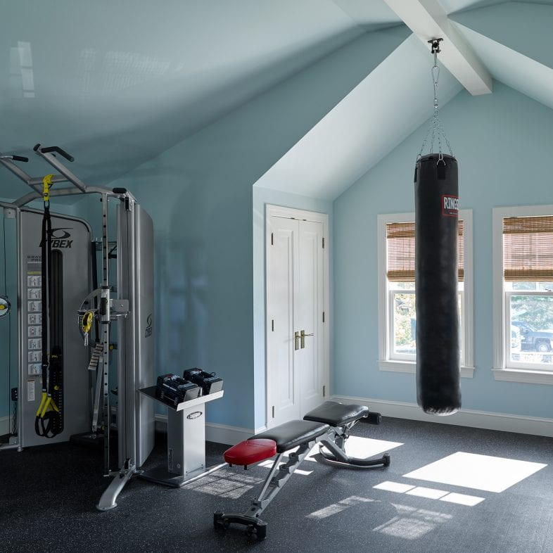 At home gym with punching bag, bench, and machines.