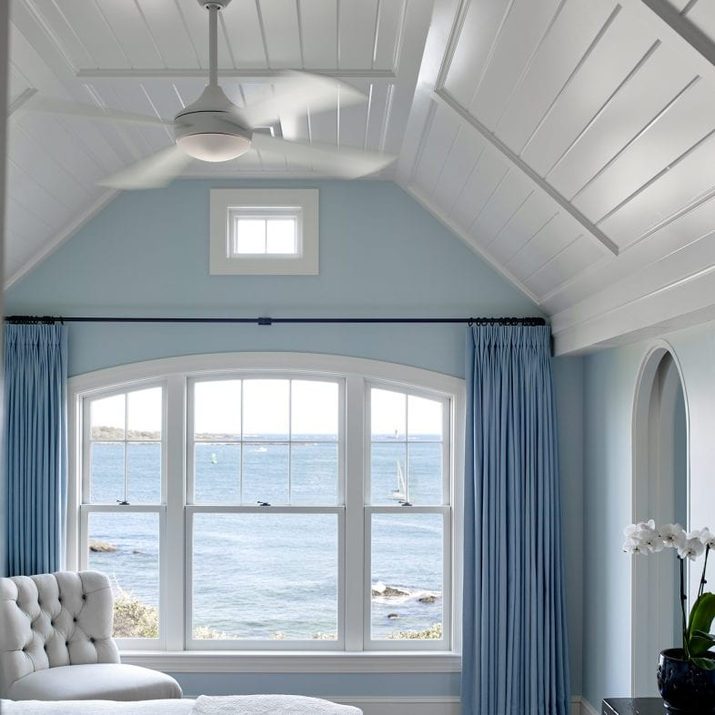 Bright and calming bedroom with modern ceiling fan and coastal views