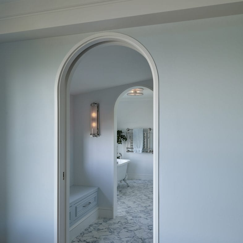 A view of the entrance to the bathroom with rounded pocket doors.