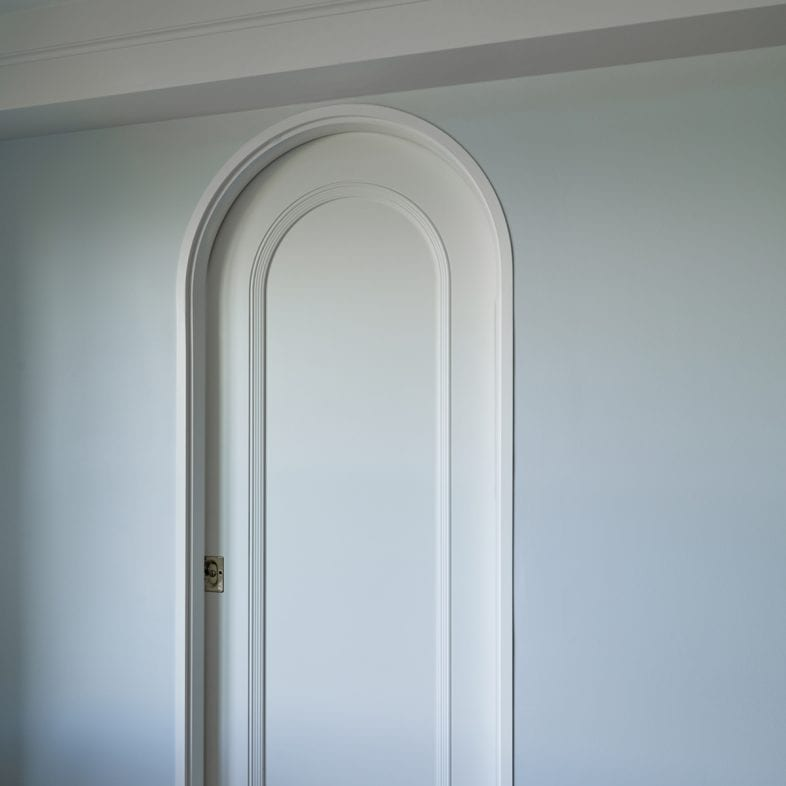 Closed rounded pocket door with white trim.