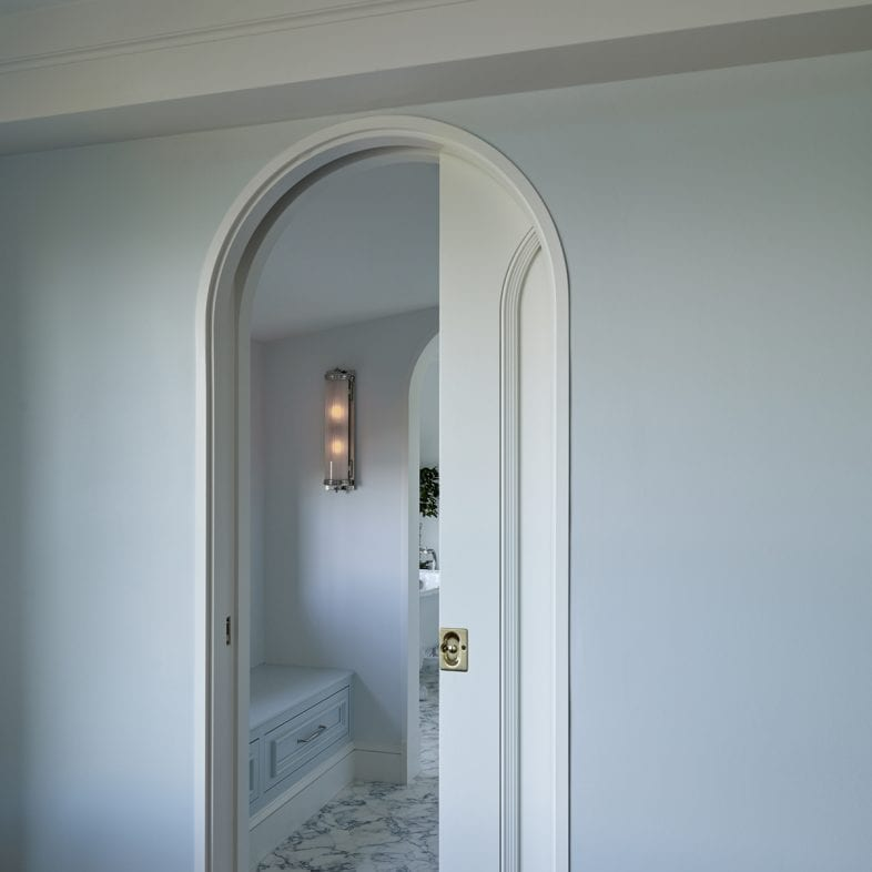 A rounded doorway with pocket doors leading to the relaxing bathroom.