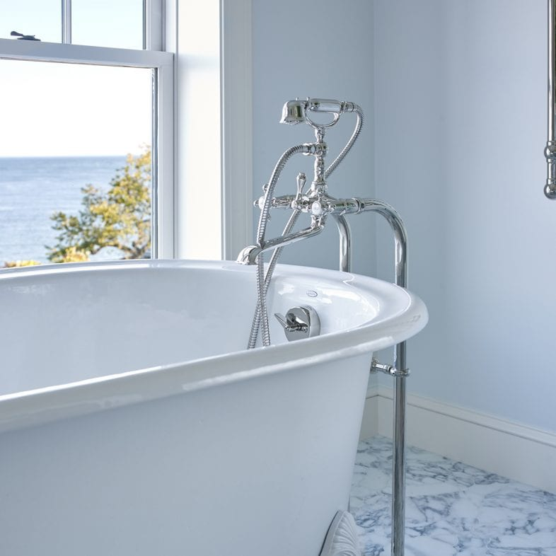 A close-up of the white clawfoot tub with vintage faucet, marble flooring, and views of the coast.