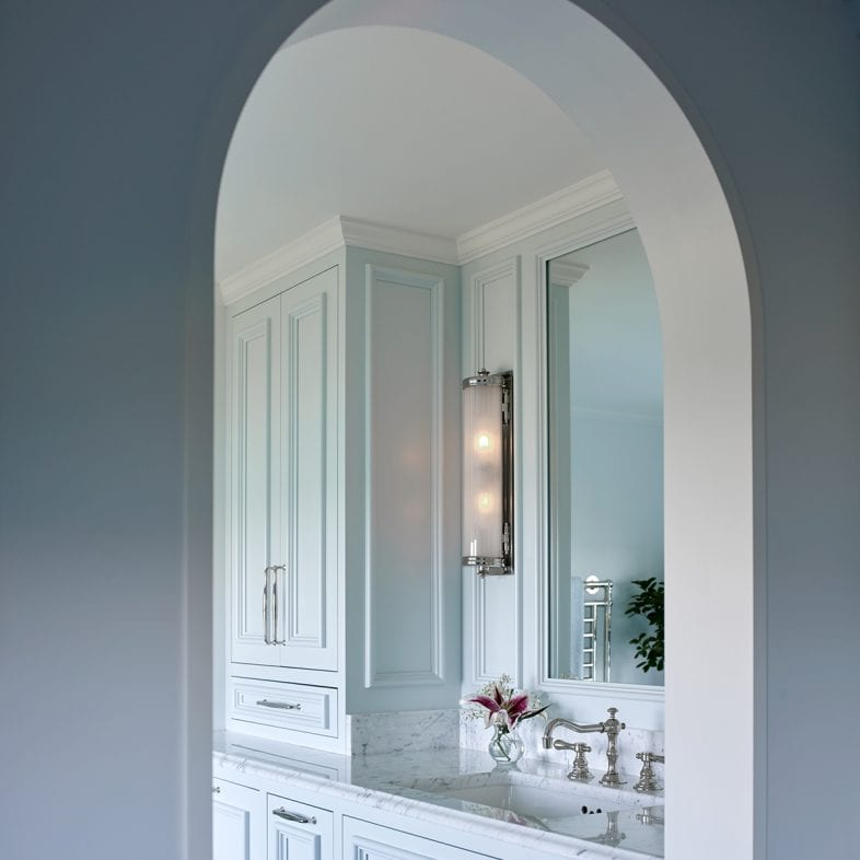 An arched doorway to the bright bathroom with marble countertops.