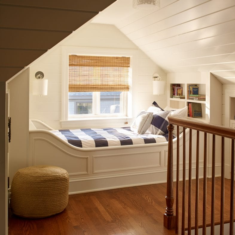 A bedroom with built-in bedframe along the window and built-in dresser.