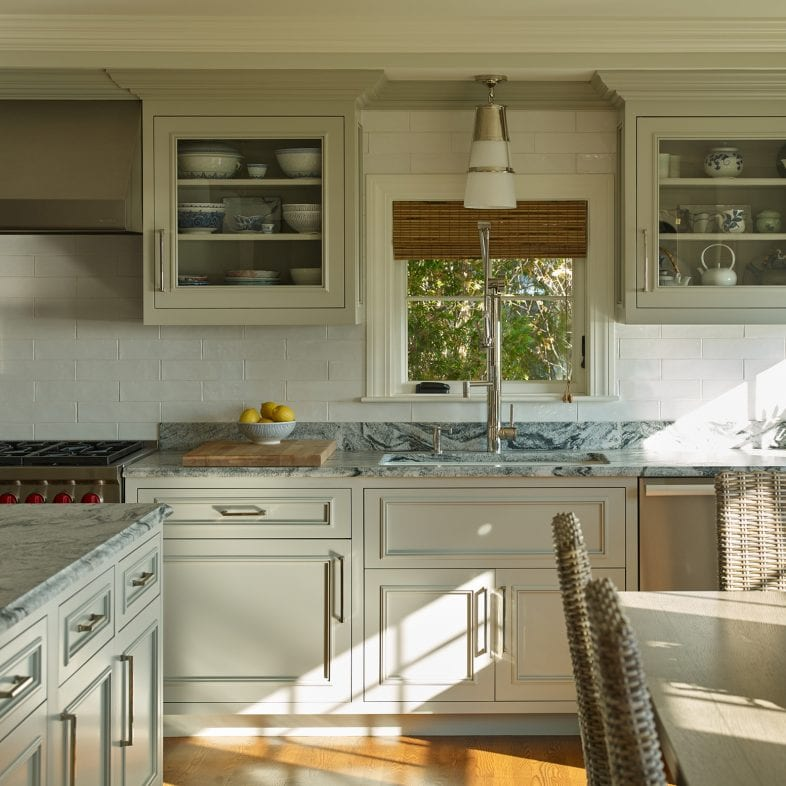 Cabinets with glass doors, marbled countertops, a large faucet and detailed molding.