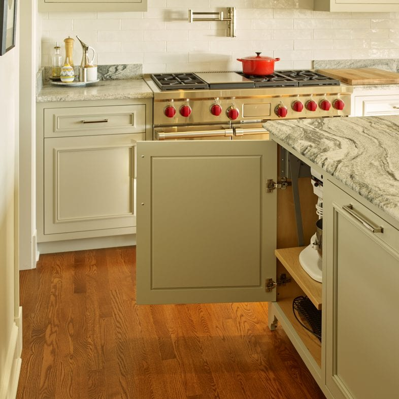 A bright kitchen with large stove, a marbled countertop with pop-up outlets and large storage space.