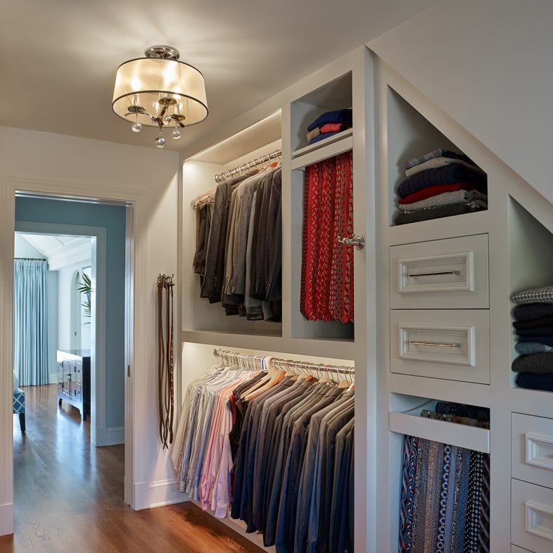 Walk-in closet with hangning racks, tie racks, and drawers for storage.
