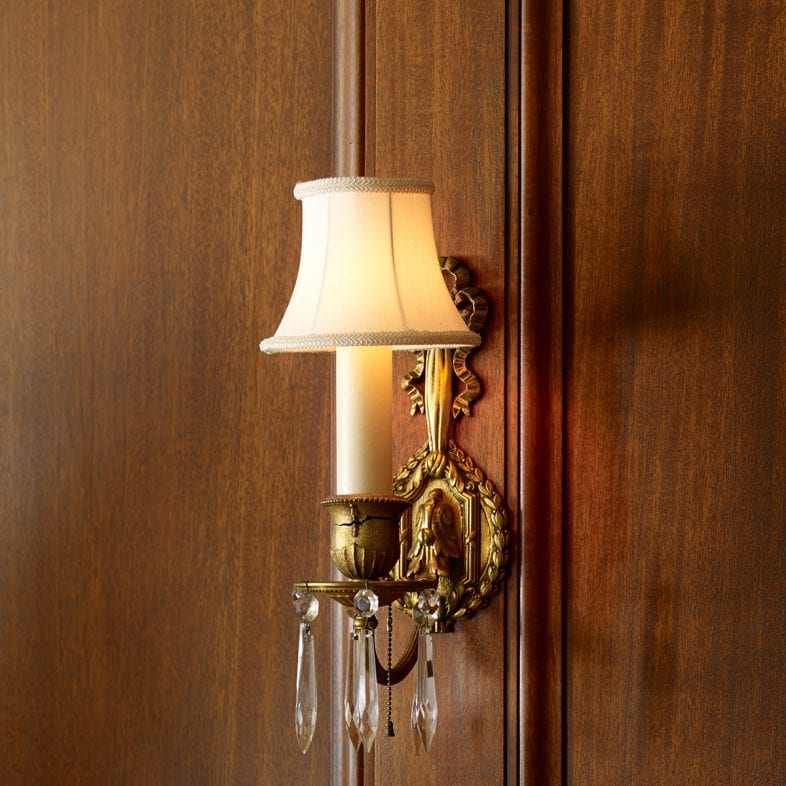 Close-up of the candlestick sconce with crystals and brass details