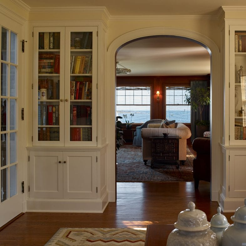 A cozy library or den space with coastal views, and built-in bookselves with glass doors.