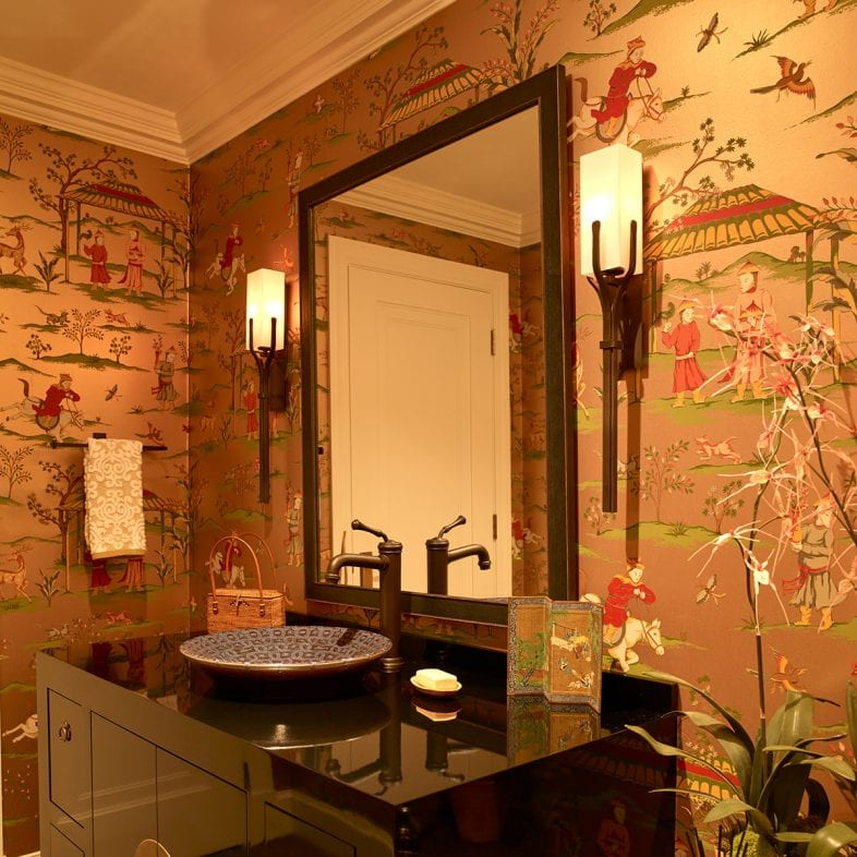 Japanese inspired bathroom with unique wallpaper, sconces, vanity, and sink.